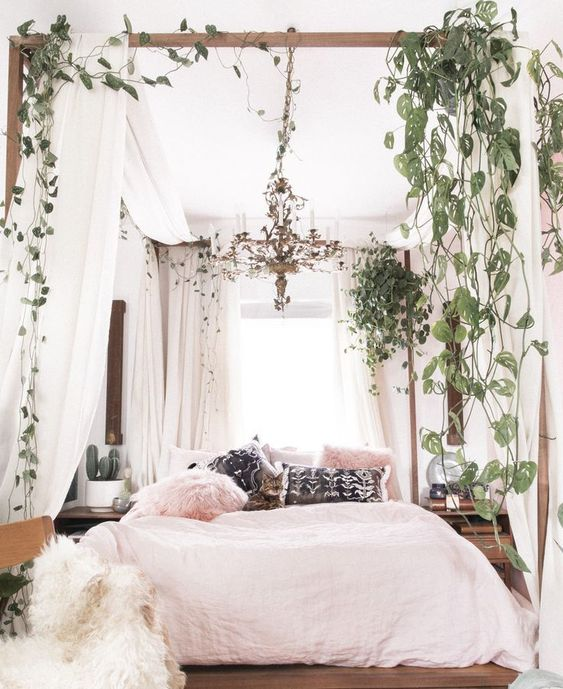 a welcoming boho bedroom with a canopy bed and climbing plants, a botanical chandelier in the center and pink bedding