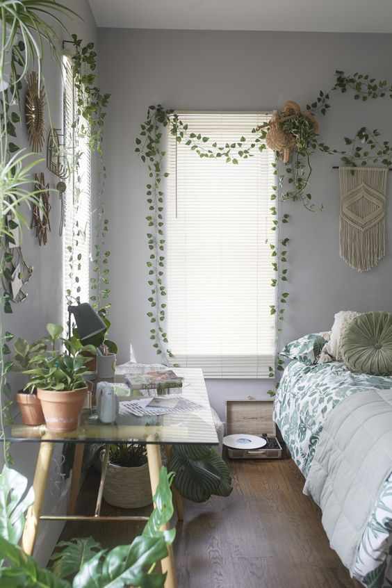 a welcoming boho bedroom with indoor vines covering the walls and some statement plants, too