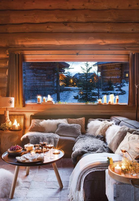 a welcoming chalet living room all clad with wood, comfy furniture, a round table and lots of candles