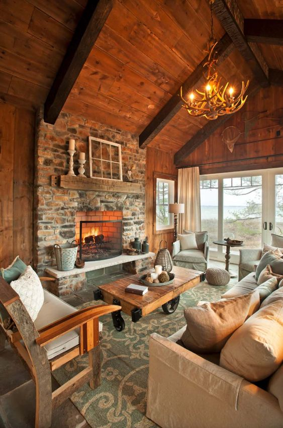 a welcoming chalet living room with a wooden ceiling and walls, a stone clad fireplace, modern and rustic furniture and an antler chandelier