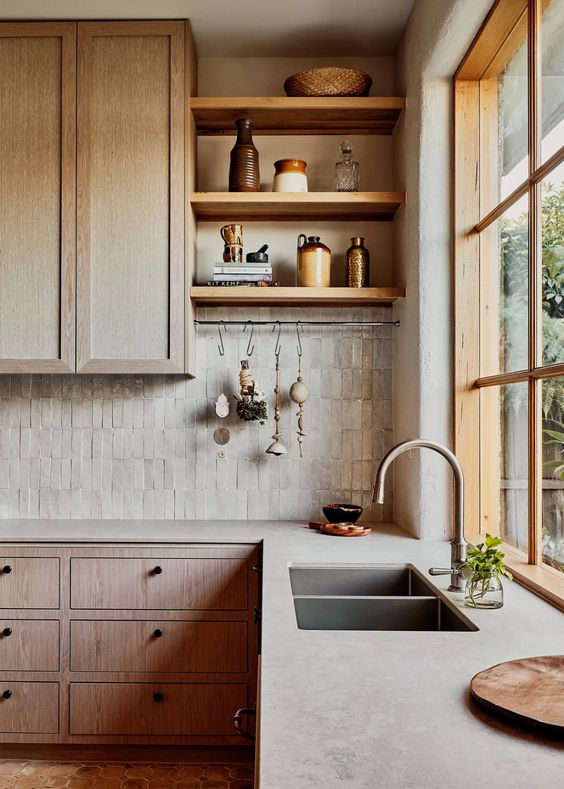 a welcoming kitchen with wooden cabinets, concrete countertops and a skinny tile backsplash plus open shelves