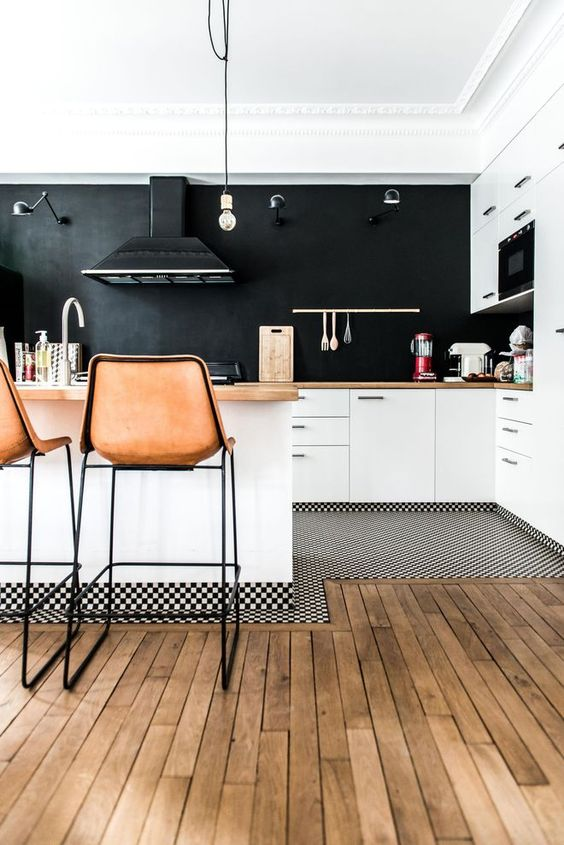 a welcoming white kitchen with butcherblock countertops and a chalkboard wall instead of a backsplash plus leather stools