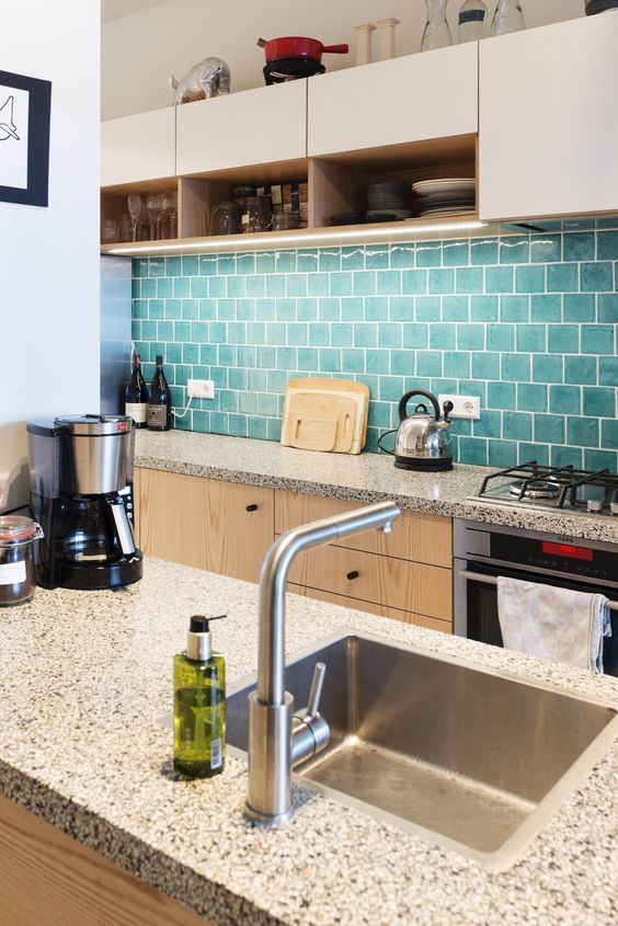 a white and blonde wood kitchen with a blue tile backsplash plus grey terrazzo countertops and built-in lights