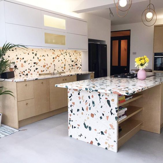 a white and light stained kitchen with a bright terrazzo backsplash and countertops on the cabinets and on the kitchen island