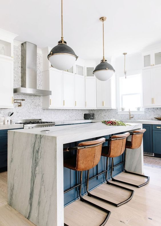 a white and navy kitchen with a navy kitchen island and a white stone waterfall countertop plus leather stools is pure chic