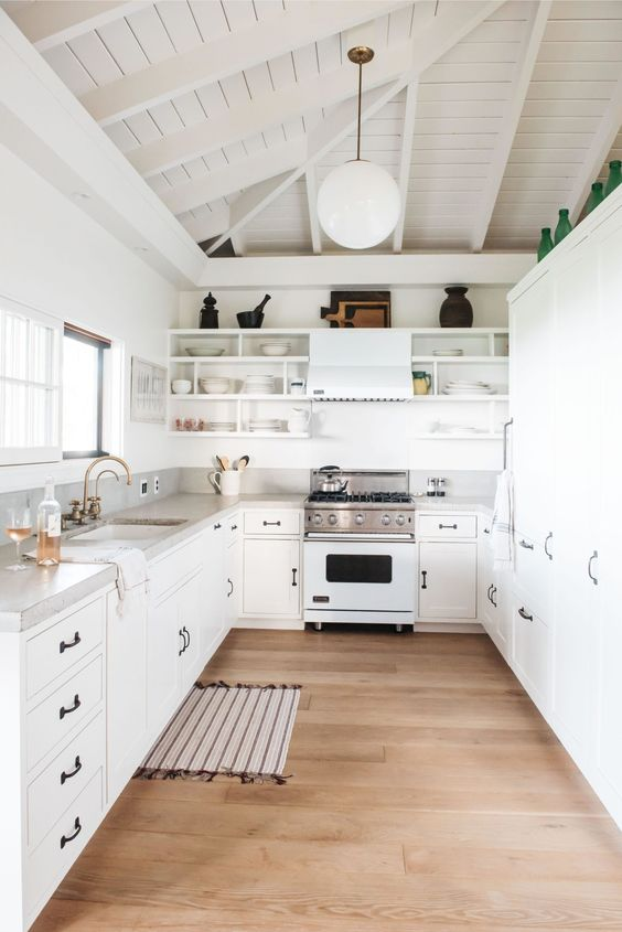 a white beach cottage kitchen with a concrete countertop and backsplash plus black handles for a chic look