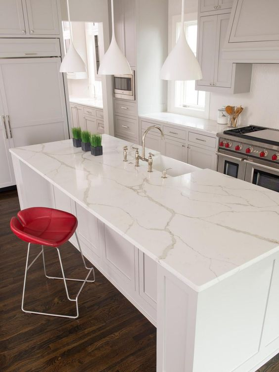 a white contemporary kitchen with cool cabinets, white quartz coutnertops, white pendant lamps and a tall red stool for an accent