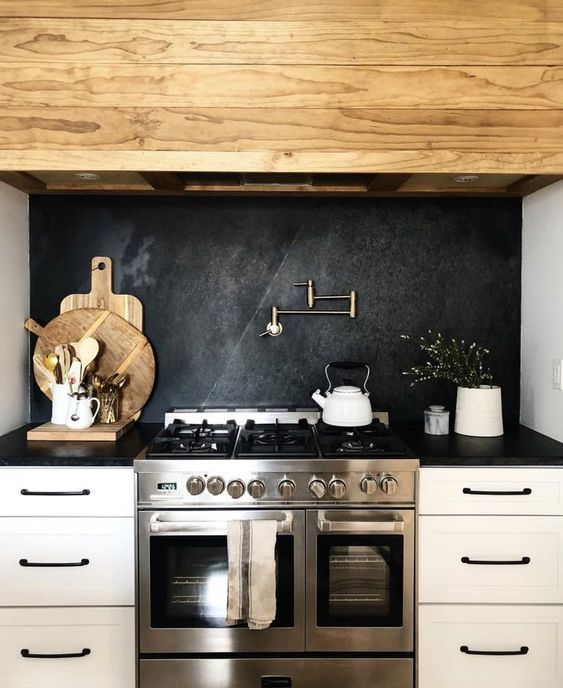 a white farmhouse kitchen with a blackened metal backsplash plus white quartz countertops and a wooden hood is welcoming