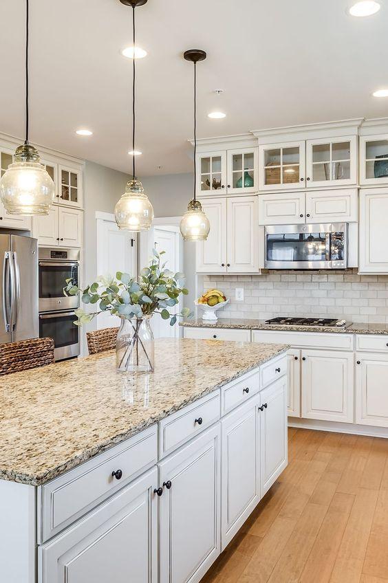 a white farmhouse kitchen with a white tile backsplash, grey granite countertops, glass pendant lamps and woven stools