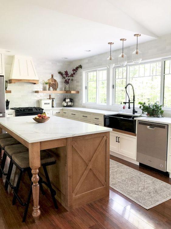 a white farmhouse kitchen with a wooden kitchen island, white quartz countertops, an elegant hood and floating shelves