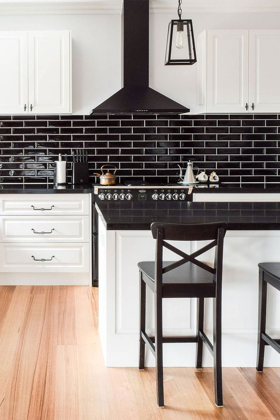 a white farmhouse kitchen with black glossy tiles, a black hood and countertops plus black stools