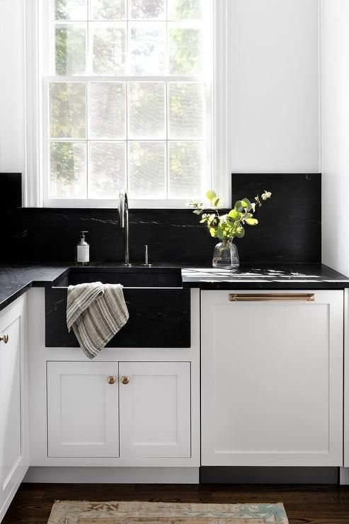 a white farmhouse kitchen with black quartz countertops and a matching backsplash plus mismatching metals for fxitures
