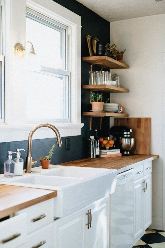 a white farmhouse kitchen with butcherblock countertops, floating shelves and a black painted backsplash plus brass fixtures