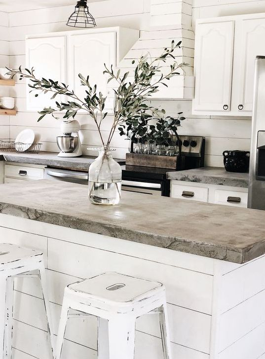 a white farmhouse kitchen with concrete countertops, a white plywood hood and shabby chic stools in white