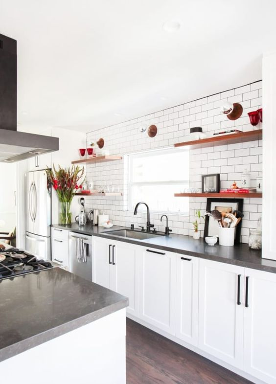 a white farmhouse kitchen with concrete countertops, black fixtures and open shelves is a welcoming space