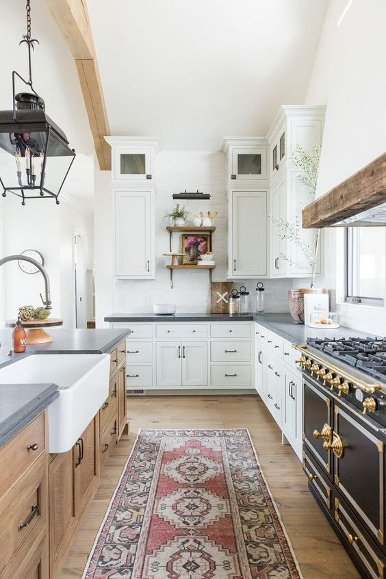 a white farmhouse kitchen with concrete coutnertops, a wooden kitchen island, a vintage cooker and gold touches