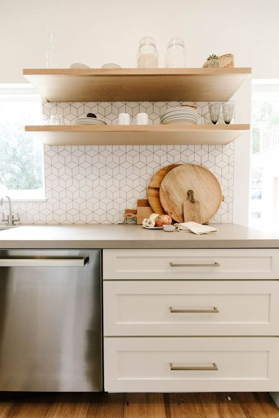 a white farmhouse kitchen with floating shelves, a white tile backsplash and a cocnrete countertop is chic and welcoming