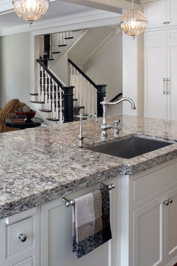 a white kitchen island with a grey granite countertop, vintage fixtures and knobs is very chic and beautiful