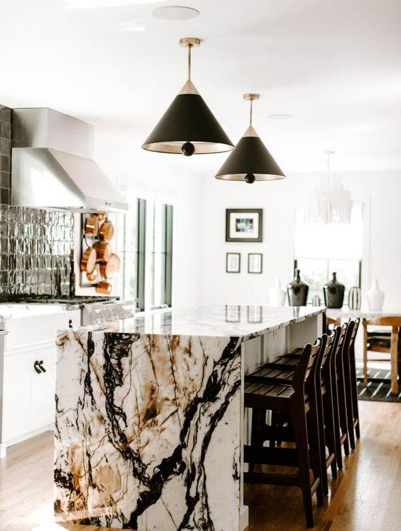 a white kitchen with a black tile backsplash and a kitchen island with a jaw-dropping waterfall countertop plus black pendant lamps