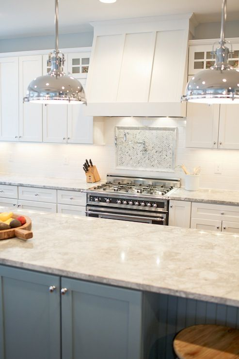 a white kitchen with a tile backsplash, a blue kitchen island and white granite countertops and retro metal pendant lamps