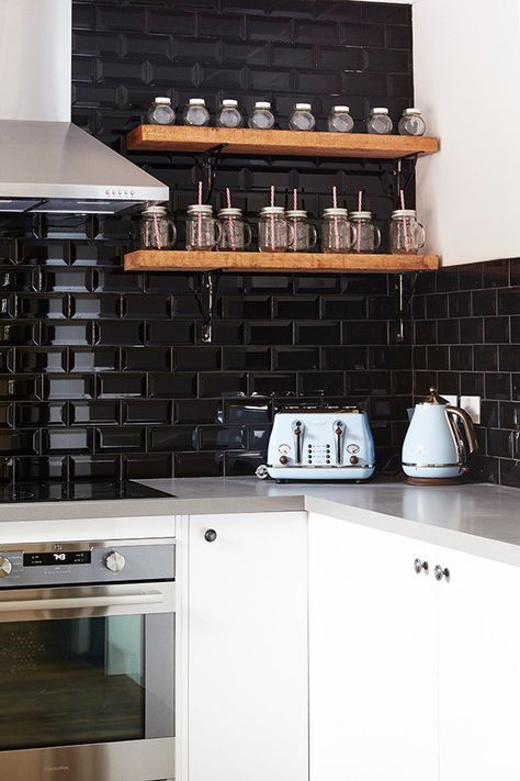 a white kitchen with grey countertops and a black glossy tile backsplash that takes two walls plus floating stained shelves for spices