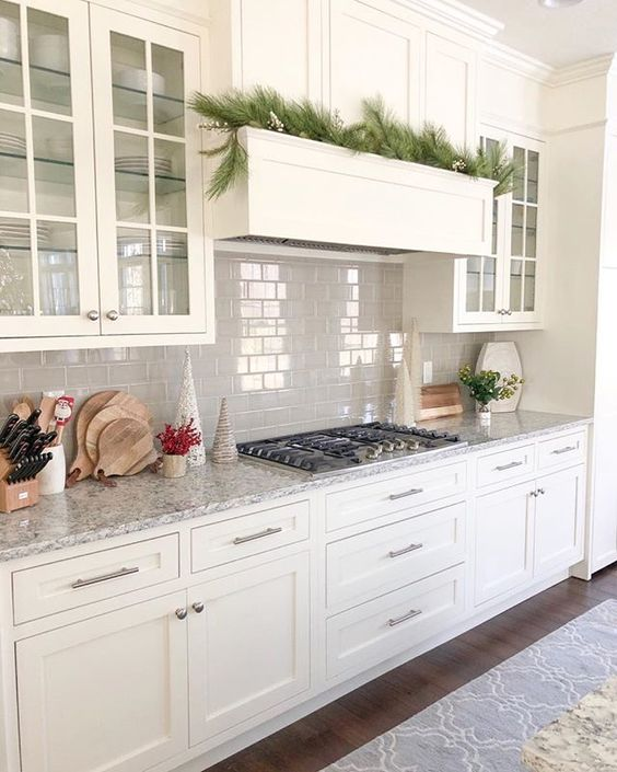 a white kitchen with shaker style cabinets, a grey tile backsplash, grey granite countertops and built-in appliances