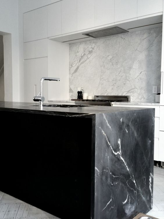 a white minimalist kitchen with a contrasting black kitchen island and a waterfall soapstone countertop is a chic idea