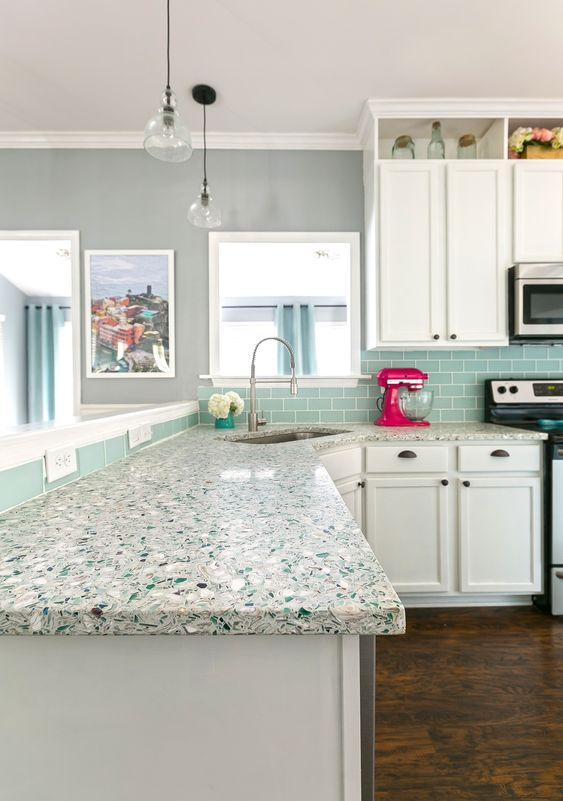 a white retro kitchen with a blue tile backsplash, a neutral terrazzo coutnertop and black handles that add a bit of contrast
