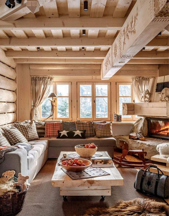 a whitewashed chalet living room all done with wood, with a wood plus stone fireplace and cozy textiles