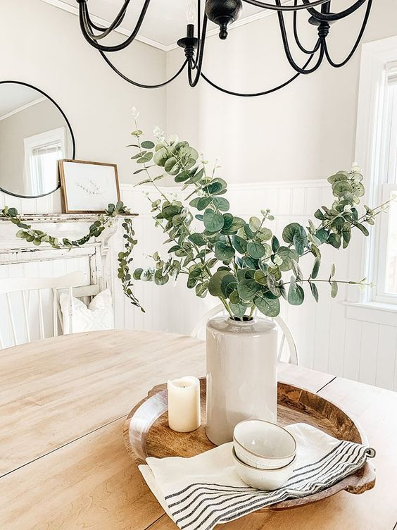 a wooden tray with a vase with eucalyptus, candles, striped napkins and bowls for spring