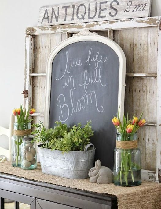 an Easter console table with a burlap runner, greenery in a bathtub, eggs in a jar, a bunny, colorful tulips in jars