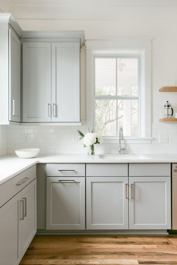 an airy and serene dove grey ktichen with a white subway tile backsplash and white quartz countertops plus stainless steel fixtures