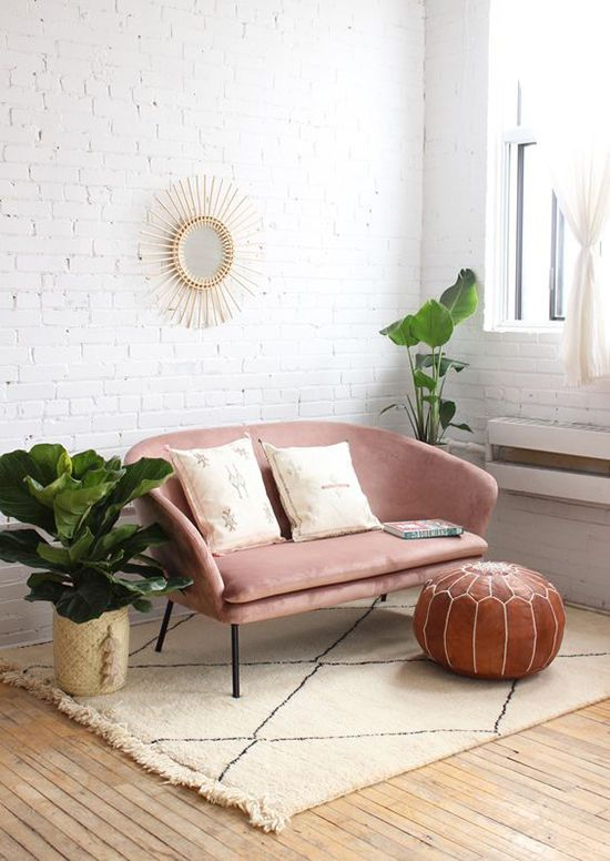 an airy boho nook with a pink loveseat on tall legs for an airier feel, potted plants and a leather ottoman is chic