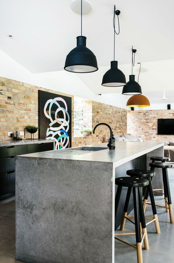 an amazing black kitchen with concrete countertops and a kitchen island with a concrete waterfall countertop and chic retro lamps