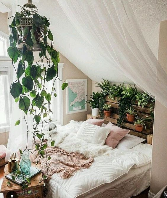 an attic boho bedroom in neutrals, with a pallet vertical garden, a climbing plant in a cage and a cozy bed