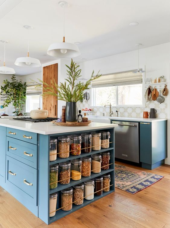 an elegant blue kitchen with white quartz countertops, a printed tile backsplash, potted greenery and gold touches
