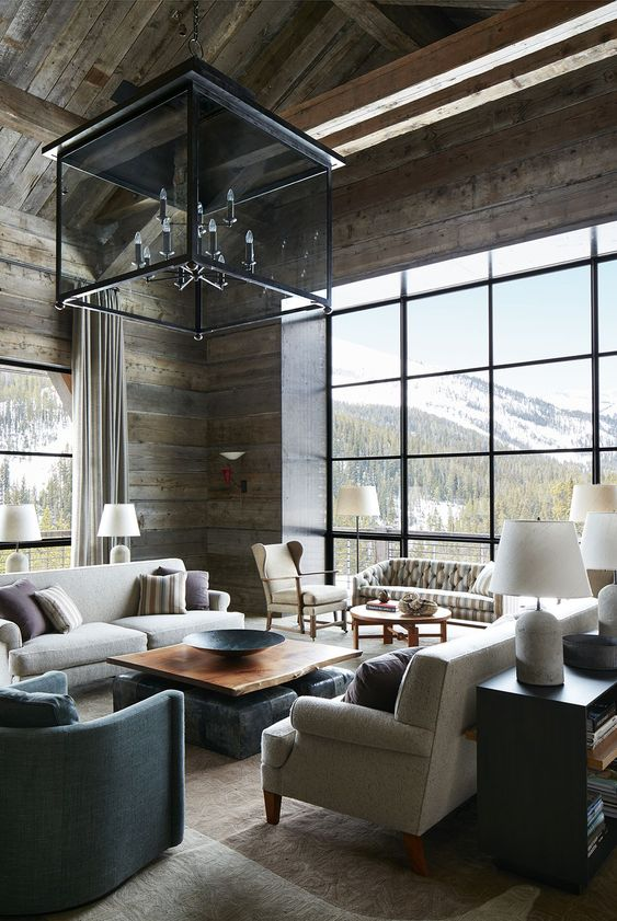 an elegant chalet living room with reclaimed wooden walls and a ceiling, neutral furniture and a large glass chandelier