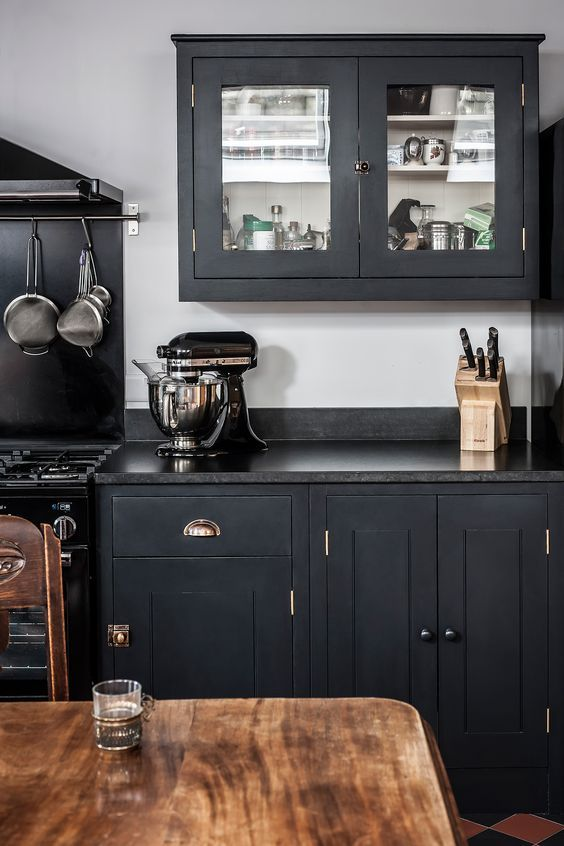 an elegant graphite grey kitchen with black countertops, elegant brass touches and black granite countertops wows