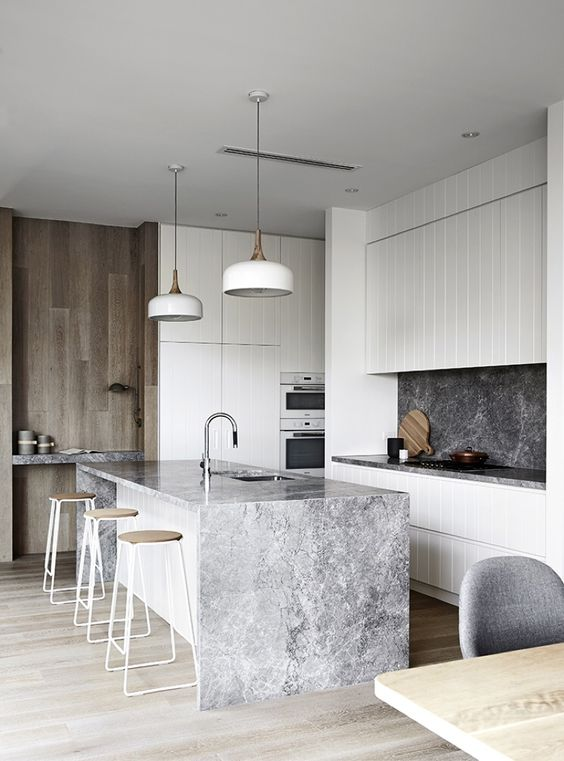 an elegant minimalist kitchen with white cabinetry, a grey stone backsplash and a waterfall countertop