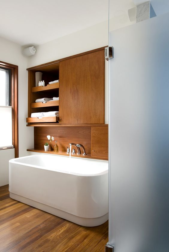 an elegant modern bathroom clad with natural wood, with a stylish tub and frosted glass in the shower