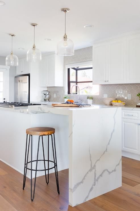 an elegant white kitchen with a grey tile backsplash and a kitchen island with a waterfall countertop as a breakfast bar