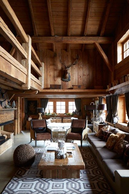 an exquisite chalet interior with wooden walls and a ceiling, with chic furniture, a reclaimed wood table and a deer head on the wall