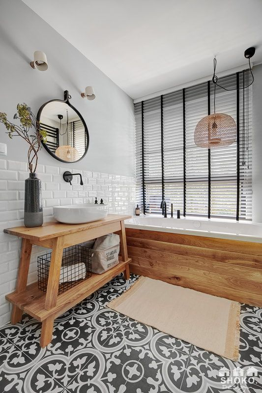 an eye-catchy bathroom with a patterned floor, a glazed wall, a tub clad with wood and a farmhouse wooden vanity