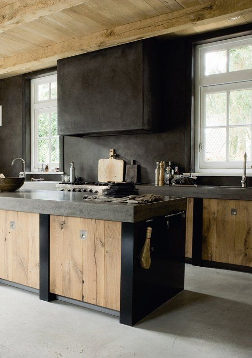 an industrial kitchen with sleek wooden cabinets, dark concrete countertops, a backsplash and a hood is a bold idea