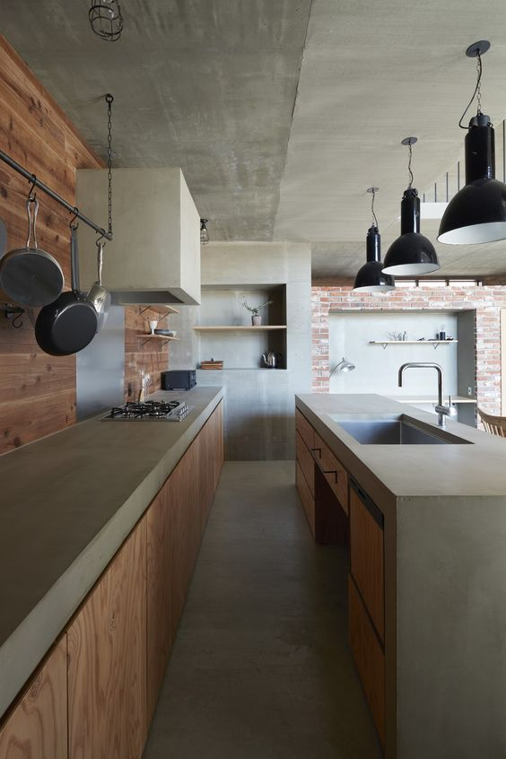 an industrial light stained kitchen with concrete coutnertops and a hood, a brick wall and a light stained wall