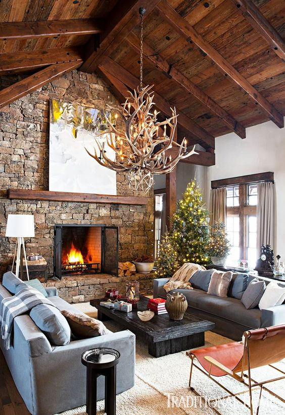 an inviting chalet living room with a wooden ceiling with beams, a stone fireplace, an antler chandelier and chic and cool furniture