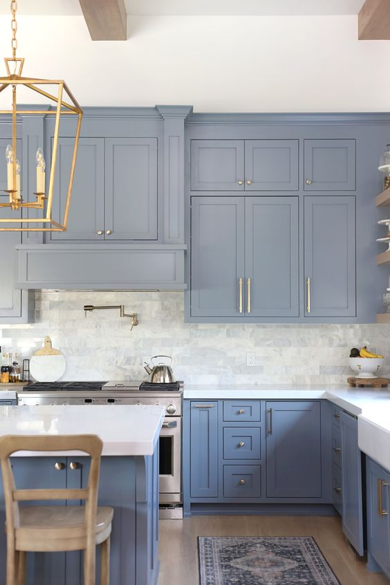 an ocean blue kitchen with a white marble tile backsplash, white quartz countertops, touches of brass and gold is pure chic