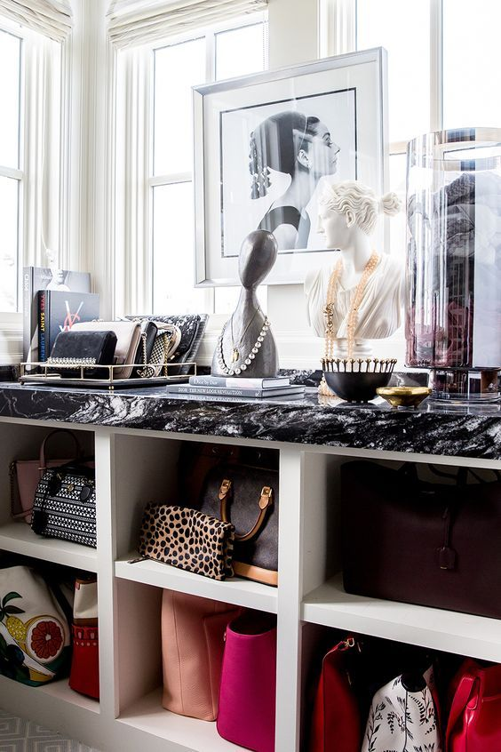 an open dresser for bags and wallets, its top is used for storing small clutches and accessories on statuettes and trays is a glam idea