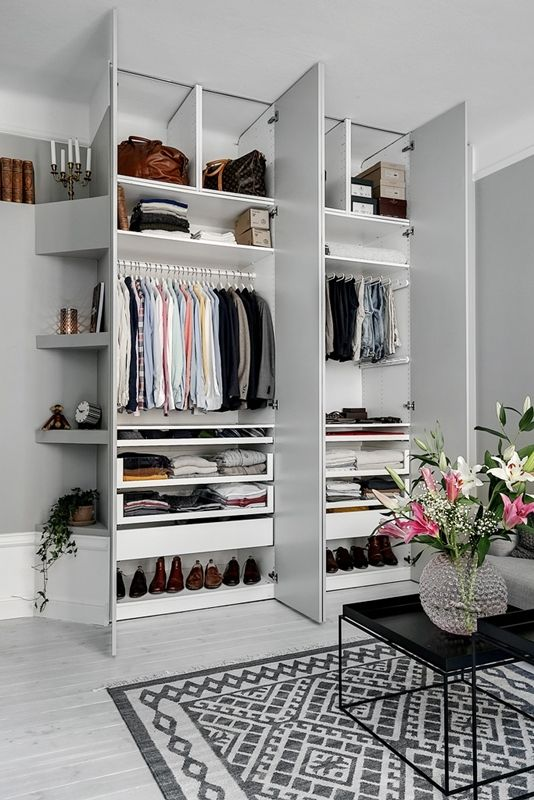 an organized closet with clothes holders, open shelves and clear and usual drawers plus boxes with shoes is a stylish idea