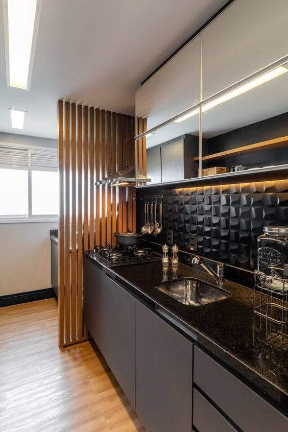 an ultra-modern kitchen in black and white, with a dimensional black tile backsplash and black coutnertops plus built-in lights